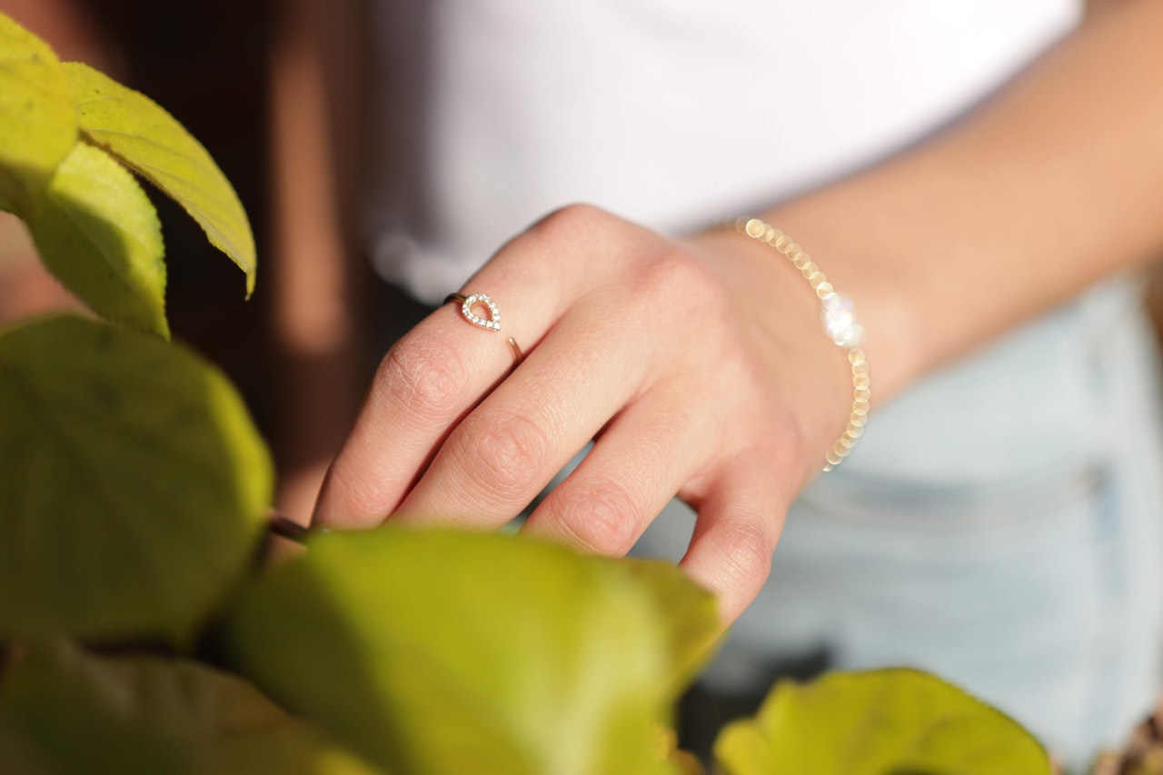 Girl in white shirt wearing a gold ring with diamond details