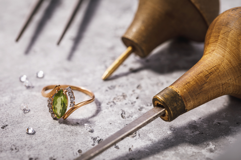 Gold ring with precious stones on the table, surrounded by jewelry repair tools, close-up
