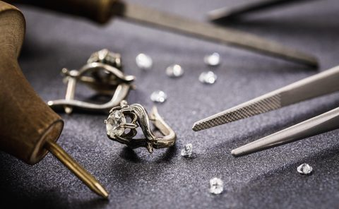 Earrings with a stone on the table, surrounded by tools for the repair of jewelry